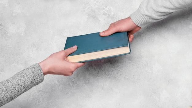 Bovenaanzicht van mensen die hardcover boek uitwisselen