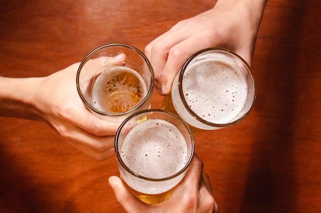 Bovenaanzicht van mensen die hun glazen met bier rammelen, aan de bar.