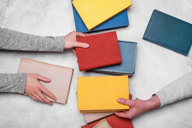 Bovenaanzicht van mensen die kleurrijke hardback-boeken uitwisselen