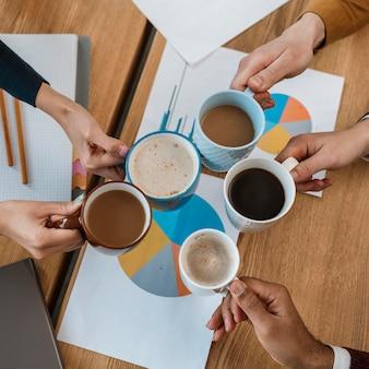 Bovenaanzicht van mensen juichen met koffiemokken tijdens kantoorvergadering