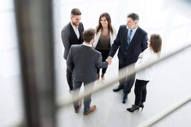 Bovenaanzicht van mensen uit het bedrijfsleven handen schudden, een vergadering afronden