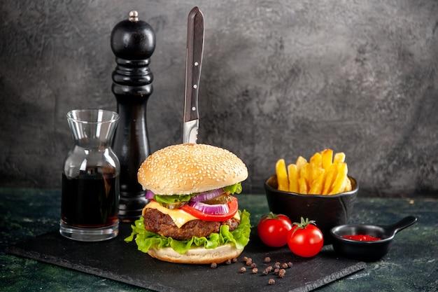 Bovenaanzicht van mes in broodje heerlijk vlees en groene paprika op zwarte dienblad saus ketchup tomaten met stam frietjes op donkere ondergrond
