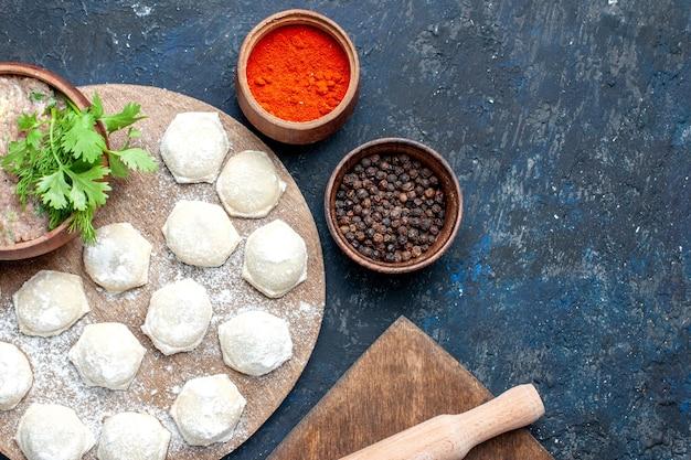 Bovenaanzicht van met bloem bestoven deegplakken met gehakt greens en paprika op donker bureau, eten rauw vlees diner gebak
