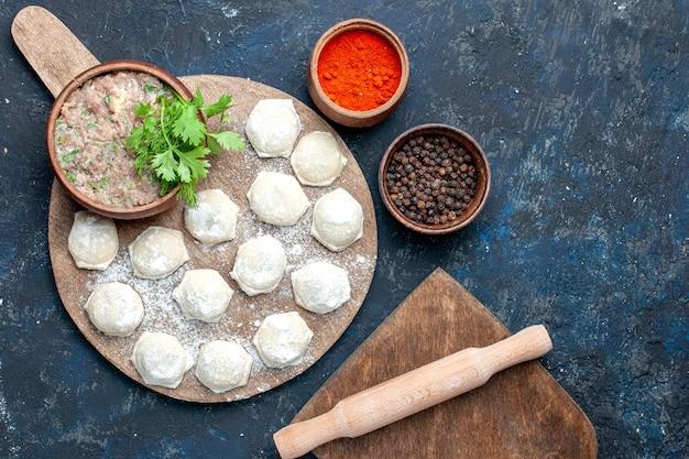 Bovenaanzicht van met bloem bestoven deegstukken met gehakt greens en paprika op donker bureau, eten rauw vlees diner gebak