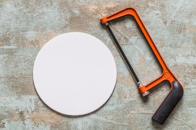 Bovenaanzicht van metaalzaag en witte circulaire frame