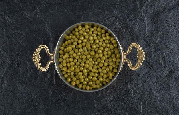Bovenaanzicht van metalen pan vol met groene erwten.