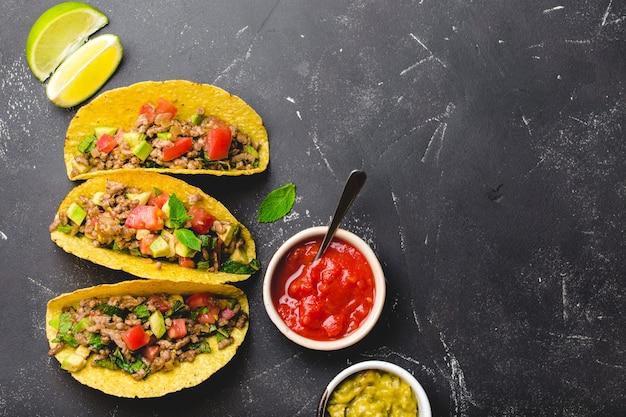 Bovenaanzicht van mexicaanse taco's met vlees, groenten in gele maïstortilla geserveerd met salsa en guacamole sauzen op zwarte rustieke stenen achtergrond