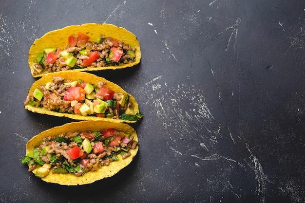 Bovenaanzicht van mexicaanse taco's met vlees, tomatensalsa, avocado, kruiden in gele maïstortilla op zwarte rustieke stenen achtergrond