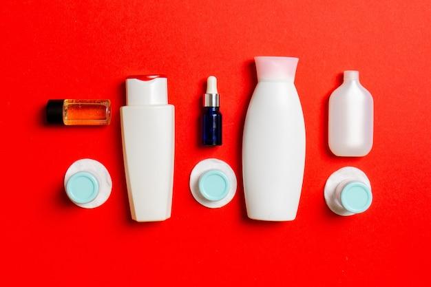 Bovenaanzicht van middelen voor gezichtsverzorging: flessen en potten met tonic, micellair reinigingswater, crème, wattenschijfjes op gekleurde achtergrond. lichaamsverzorgingsconcept met lege ruimte voor uw ideeën.