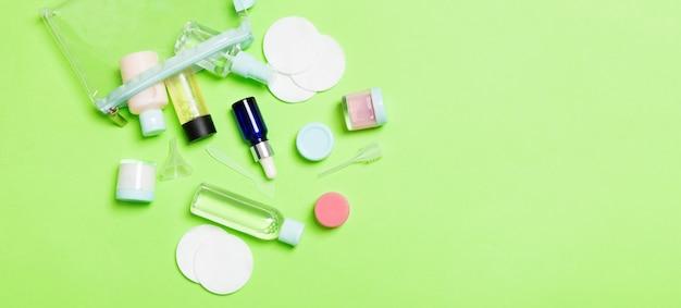 Bovenaanzicht van middelen voor gezichtsverzorging: flessen en potten met tonic, micellair reinigingswater, crème, wattenschijfjes op groene achtergrond. lichaamsverzorgingsconcept met lege ruimte voor uw ideeën.