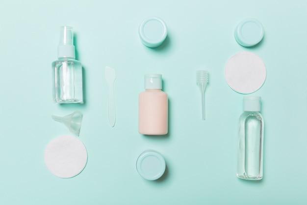 Bovenaanzicht van middelen voor gezichtsverzorging: flessen en potten tonic, micellair reinigingswater, crème, wattenschijfjes op blauw. bodycare concept met lege ruimte voor uw ideeën
