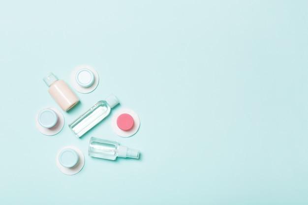 Bovenaanzicht van middelen voor gezichtsverzorging: flessen en potten tonic, micellair reinigingswater, crème, wattenschijfjes op blauwe achtergrond. lichaamsverzorging concept met lege kopie ruimte voor uw ideeën
