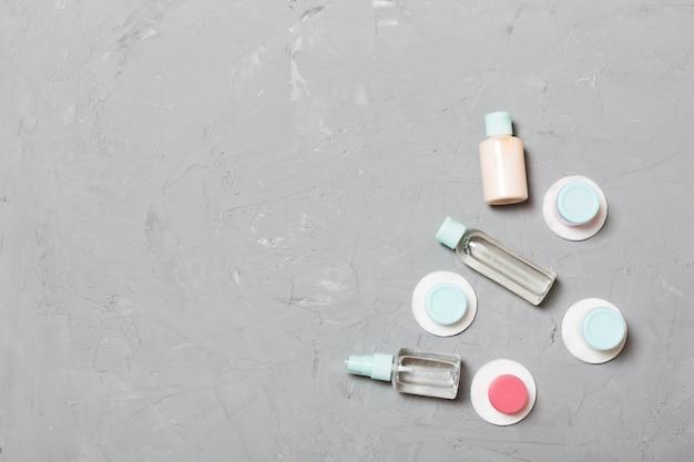 Bovenaanzicht van middelen voor gezichtsverzorging: flessen en potten tonic, micellair reinigingswater, crème, wattenschijfjes op grijs. bodycare concept met lege ruimte voor uw ideeën