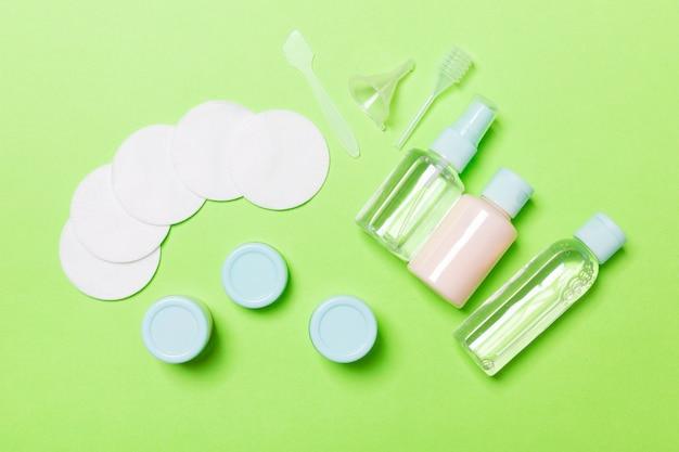 Bovenaanzicht van middelen voor gezichtsverzorging: flessen en potten tonic, micellair reinigingswater, crème, wattenschijfjes op groen. bodycare concept met lege ruimte voor uw ideeën