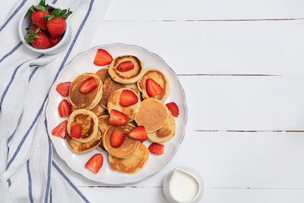 Bovenaanzicht van mini pannenkoeken met aardbeien op witte houten tafel