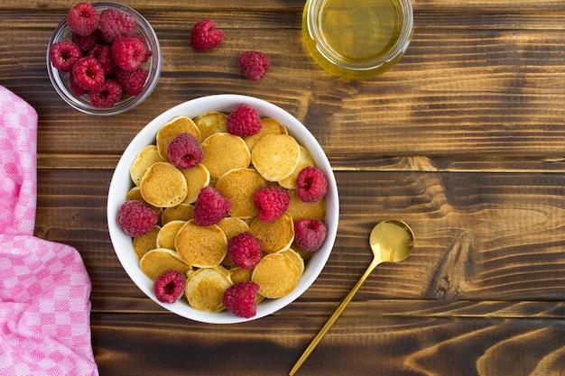 Bovenaanzicht van mini pannenkoeken met frambozen in de witte kom op de houten tafel