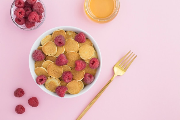Bovenaanzicht van mini pannenkoeken met frambozen in de witte kom op het roze oppervlak