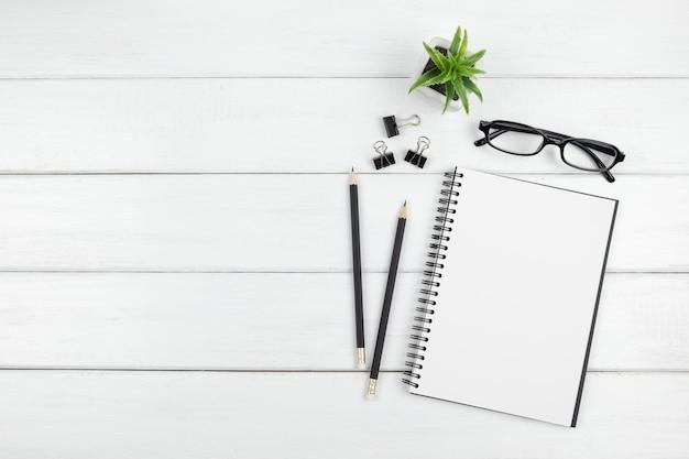 Bovenaanzicht van minimaal bureau met een open lege notebook en briefpapier items