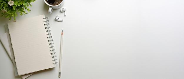 Bovenaanzicht van minimale studie tafel met kopie ruimte notebooks potlood en kopje op wit bureau