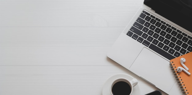Bovenaanzicht van minimale werkplek met laptop, koffiekopje en kantoorbenodigdheden