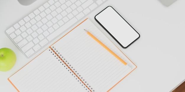 Bovenaanzicht van minimale werkplek met smartphone met leeg scherm