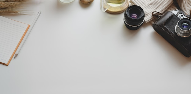 Bovenaanzicht van minimale werkplek met vintage camera- en kantoorbenodigdheden met decoraties