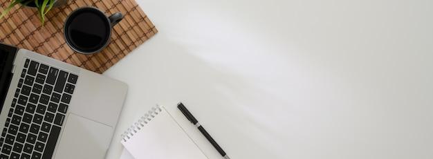 Bovenaanzicht van minimale werkruimte met laptop, notebook, koffiekopje op bamboe mat en kopie ruimte