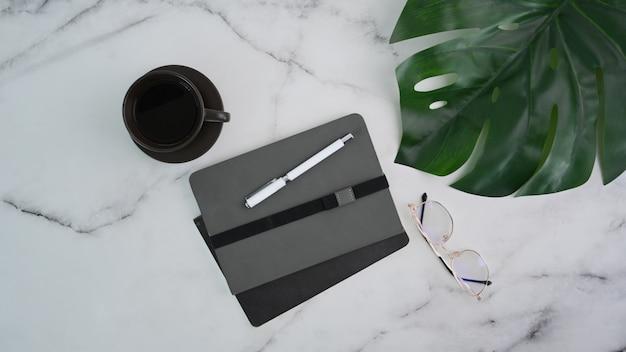 Bovenaanzicht van minimale werkruimte met notebook, bril en koffie op marmeren tafel.