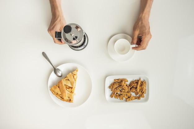 Bovenaanzicht van minimalistische tafel met zakenlunch met koffie, ontbijtgranen en appeltaart.