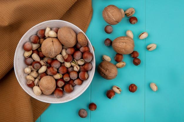 Bovenaanzicht van mix noten in een kom met walnoten, hazelnoten met pistachenoten met een bruine handdoek op een turquoise ondergrond