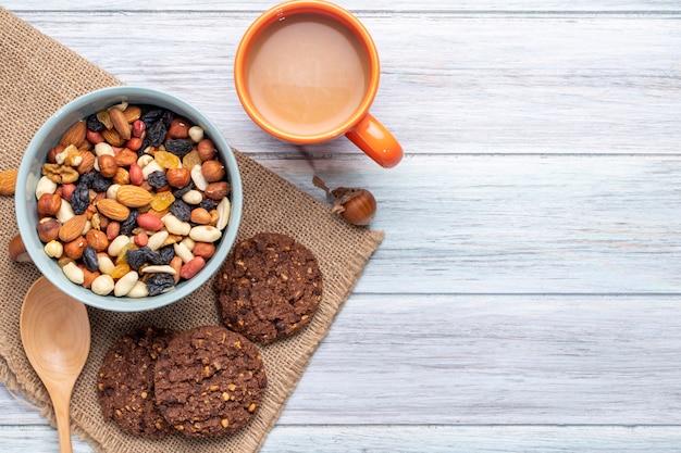 Bovenaanzicht van mix van noten en gedroogde vruchten in een kom en havermout koekjes met een mok cacaodrank op rustiek