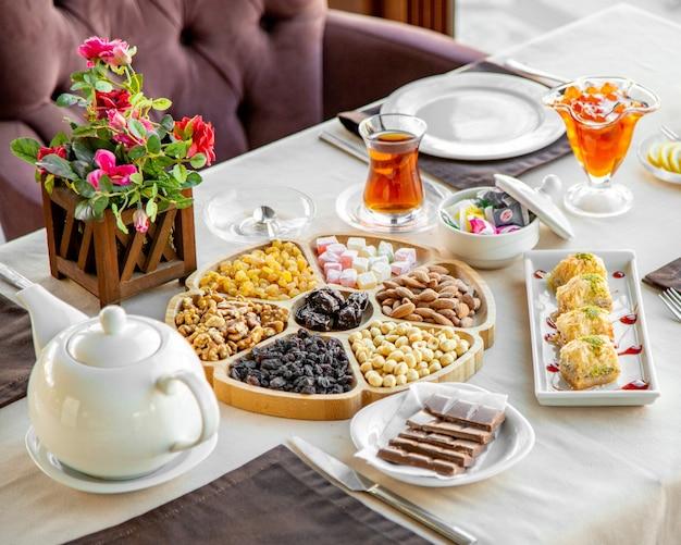 Bovenaanzicht van mix van noten met gedroogde vruchten op een houten plaat geserveerd met thee en snoep op tafel in restaurant