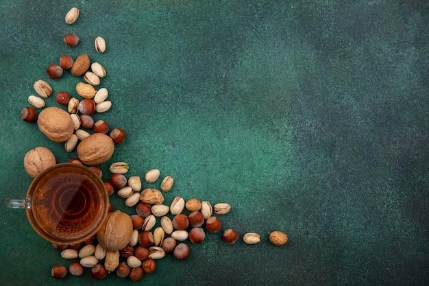 Bovenaanzicht van mix van noten, walnoten, pistachenoten, hazelnoten en pinda's met een kopje thee op een groene ondergrond