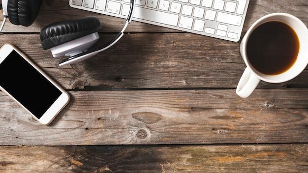Bovenaanzicht van mobiel; hoofdtelefoon en toetsenbord met koffiekopje