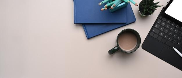 Bovenaanzicht van mock up digitale tablet, koffiekopje, briefpapier en notebook op beige crème tafel. ruimte kopiëren.
