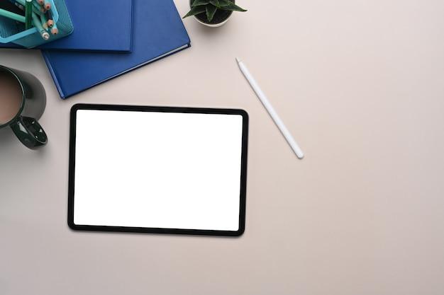 Bovenaanzicht van mock up digitale tablet met leeg scherm, stylus pen, koffiekopje en notebook op beige crème tafel.
