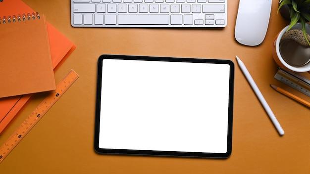 Bovenaanzicht van mock-up digitale tafel met leeg scherm, koffiekopje en notebook op oranje achtergrond.