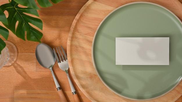 Bovenaanzicht van mock up kaart op mock up keramische plaat en zilverwerk op houten eettafel