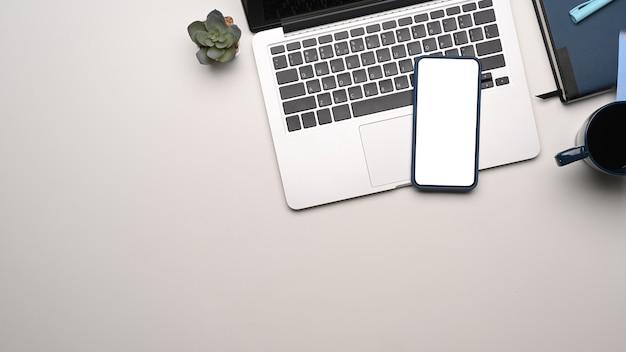 Bovenaanzicht van mock-up smartphone met leeg scherm op laptopcomputer op modern werkstation en kopieerruimte.