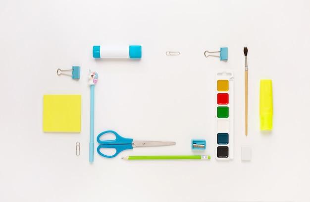 Bovenaanzicht van modern wit, blauw, geel kantoorbureaublad met schoolbenodigdheden en briefpapier op tafel rond lege ruimte voor tekst. terug naar school concept plat lag met mockup