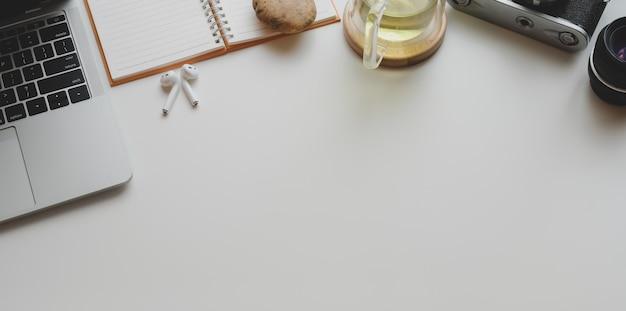 Bovenaanzicht van moderne fotograaf werkplek met laptop, kopje thee en kantoorbenodigdheden