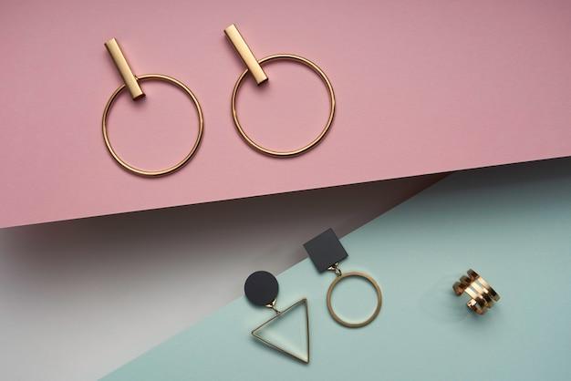 Bovenaanzicht van moderne oorbellen en ring op roze en blauw papier achtergrond