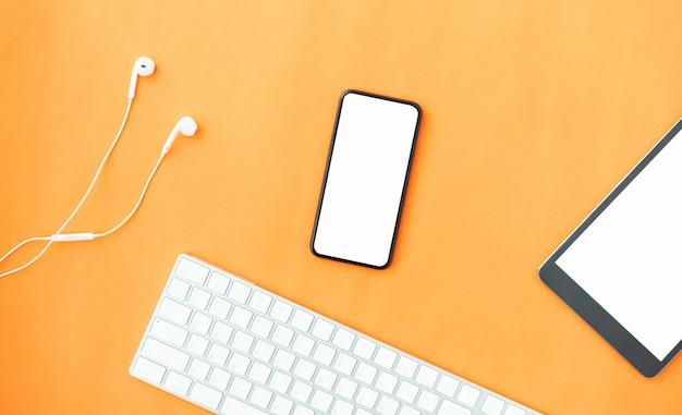 Bovenaanzicht van moderne smartphone, tablet en witte koptelefoon op oranje kleur achtergrond.
