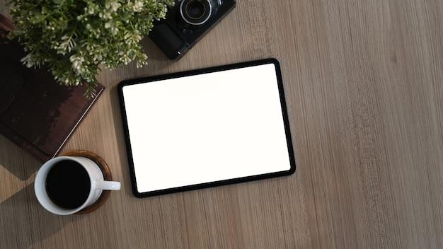 Bovenaanzicht van moderne werkplek met koffiekopje, plant, boek en tablet op houten bureau. leeg scherm voor productmontage.