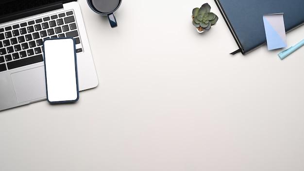 Bovenaanzicht van moderne werkruimte met mock-up laptop en smartphone met leeg scherm op witte tafel. ruimte kopiëren.