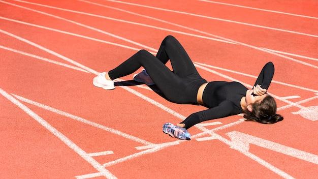 Bovenaanzicht van moe fit vrouw in sportkleding rusten na de training of hardlopen op een loopband rubberen stadion
