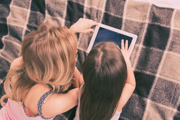 Bovenaanzicht van moeder en dochter liggend op bed en spelen met tablet
