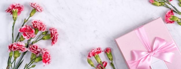 Bovenaanzicht van moederdag achtergrondontwerpconcept met anjer bloemboeket op marmeren tafel