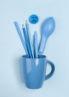 Bovenaanzicht van mok met droevig gezicht en ballon voor blauwe maandag