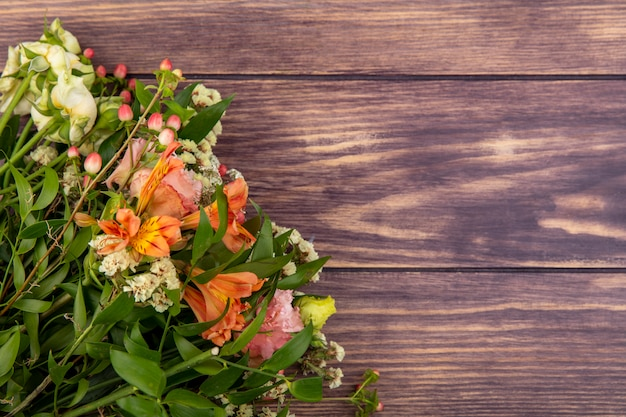 Bovenaanzicht van mooi boeket van kleurrijke bloemen met bladeren op hout